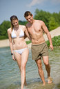 Happy couple in swimwear walk in lake Royalty Free Stock Photo