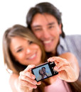 Happy couple taking a picture of themselves with camera isolated Royalty Free Stock Photo