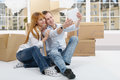 Happy couple taking selfie in their new house sitting on the floor Royalty Free Stock Images