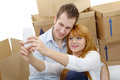 Happy couple taking selfie in their new house sitting on the floor Royalty Free Stock Photo