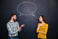 Happy couple talking over chalkboard background with drawn dialogue Royalty Free Stock Photo