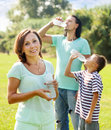 Happy couple with teenager drinking from bottles child plastic in summer park Royalty Free Stock Photo