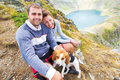 Happy couple with their dog in the mountains attractive out sitting on a rock together smiling happily as they enjoy nature and Royalty Free Stock Images