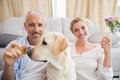 Happy couple with their pet dog drinking champagne at home in the living room Royalty Free Stock Photos