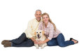 Happy couple with their pet dog on white background Royalty Free Stock Images