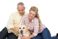 Happy couple with their pet dog on white background Royalty Free Stock Photo