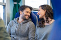 Happy couple traveling by train closeup of young together they are looking at each other while smiling and enjoy the trip they are Stock Image
