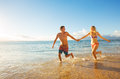 Happy couple on tropical beach at sunset running vacation Stock Photography