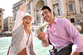 Happy couple trying tradition in trevi fountain of tourists throwing coins water Royalty Free Stock Images