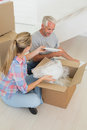 Happy couple unpacking cardboard moving boxes in their new home Stock Image