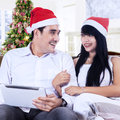 Happy couple using a digital tablet in santa s hats Royalty Free Stock Photos