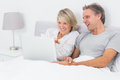 Happy couple using laptop in bed together at home Stock Images