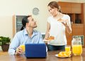 Happy couple using laptop during breakfast wife serves her beloved man he working with Stock Photo
