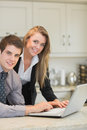 Happy couple using laptop in kitchen Stock Photos