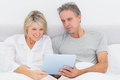 Happy couple using tablet pc in bed together at home bedroom Royalty Free Stock Image