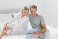 Happy couple using their digital tablet at home in bedroom Stock Photo