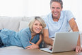 Happy couple using their laptop looking at camera home on the couch Royalty Free Stock Photo