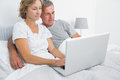 Happy couple using their laptop together in bed at home bedroom Royalty Free Stock Image