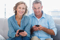 Happy couple using their smartphones looking at camera at home in the living room Royalty Free Stock Images