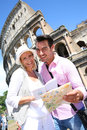 Happy couple visiting coliseum in rome reading guide book by the Stock Photos