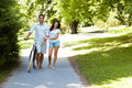 Happy couple walking with bicycle in a park Stock Image