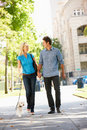 Happy Couple Walking dog down street Royalty Free Stock Photography