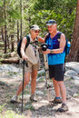 Happy couple walking outdoors in forest on hiking trail sequoia national park california she has a pole and they are looking at Stock Image