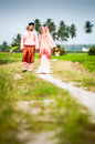Happy couple walking at padi field newly wedded on path Stock Photo