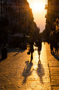 Happy couple walking at sunset in a street Royalty Free Stock Images