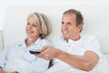 Happy couple watching television senior lying on bed Royalty Free Stock Photos