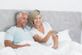 Happy couple watching tv in bed mature at home Royalty Free Stock Image