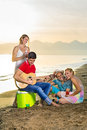 Happy couples enjoying their drinks at the beach young while playing guitar instrument Royalty Free Stock Photography