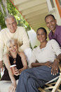 Happy couples sitting together outdoors portrait of middle aged multiethnic Royalty Free Stock Photos