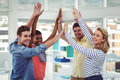 Happy creative team giving high fives to each other in casual office Stock Image