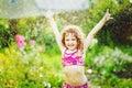 Happy curly girl under water splashes in the summer garden instagram filter Stock Photography