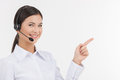 Happy customer service representative beautiful young female in headset pointing away and looking at camera while isolated on Stock Images