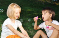 Happy cute children playing with bubbles Stock Photos