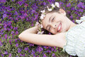 Happy cute girl wearing garland crown lying on field portrait of of flowers Stock Images