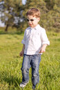 Happy cute kid walking by the grass of sunny field with sunglasses a Stock Photo