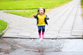 Happy cute little girl jumping in puddle after rain in summer Royalty Free Stock Photo