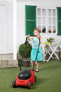 Happy cute little girl mows lawn by red lawn mower next to white house Stock Images