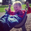 Happy cute toddler boy swinging in the swing at the park Stock Images