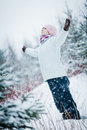 Happy cute woman enjoying winter in forest during a snowy day Stock Image