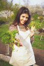 Happy cute woman giving fresh vegetables at you in garden Royalty Free Stock Photo
