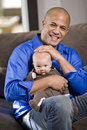 Happy dad with baby sitting on lap Royalty Free Stock Photos