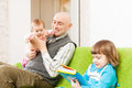 Happy dad with daughters and two sitting on couch Royalty Free Stock Photography