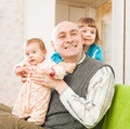 Happy dad with daughters and two sitting on couch Royalty Free Stock Photo