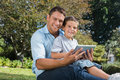 Happy dad and son with a tablet pc smiling in park Stock Photography