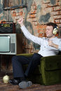 Happy dancing man in big headphones listens old radio and sits armchair very house Stock Photos