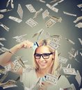 Happy debt free young woman holding a credit card cut in two pieces under money rain Royalty Free Stock Photo
